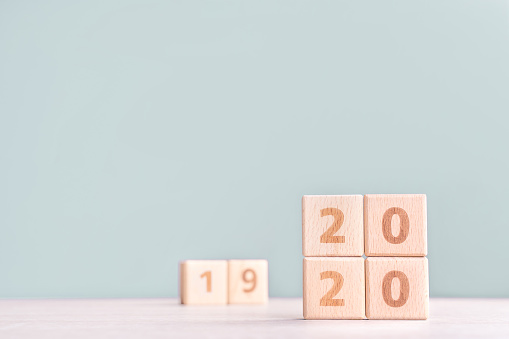 1163501702 istock photo Abstract 2020 & 2019 New year countdown design concept - wood blocks cubes on wooden table and low saturation green background. 1176676739
