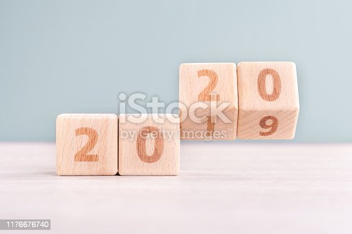 1054929988 istock photo Abstract 2020 & 2019 New year countdown design concept - wood blocks cubes on wooden table and low saturation green background. 1176676740