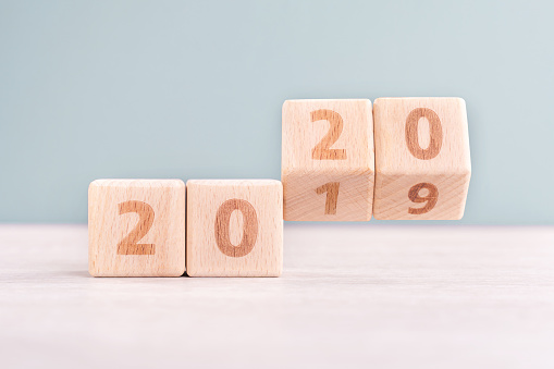 1163501702 istock photo Abstract 2020 & 2019 New year countdown design concept - wood blocks cubes on wooden table and low saturation green background. 1176676740