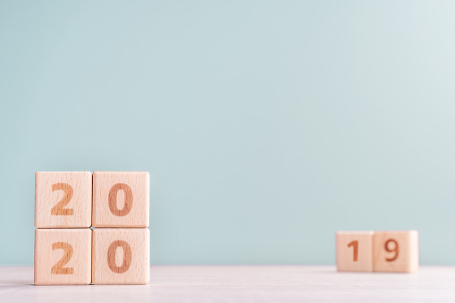 1163501702 istock photo Abstract 2020 & 2019 New year countdown design concept - wood blocks cubes on wooden table and low saturation green background. 1176676741