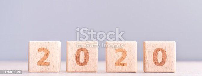 istock Abstract 2020, 2019 New year target plan design concept - wood blocks cubes on wooden table and pastel blue background, close up, blank copy space. 1179811056