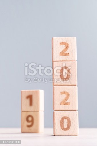1054929988 istock photo Abstract 2020, 2019 New year target plan design concept - wood blocks cubes on wooden table and pastel blue background, close up, blank copy space. 1179811066