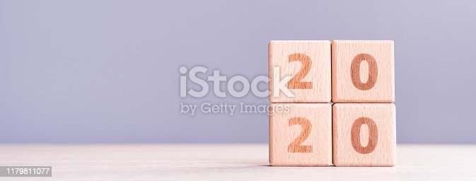 istock Abstract 2020, 2019 New year target plan design concept - wood blocks cubes on wooden table and pastel blue background, close up, blank copy space. 1179811077