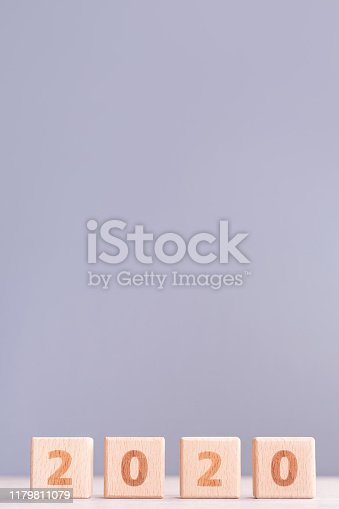 1054929988 istock photo Abstract 2020, 2019 New year target plan design concept - wood blocks cubes on wooden table and pastel blue background, close up, blank copy space. 1179811079
