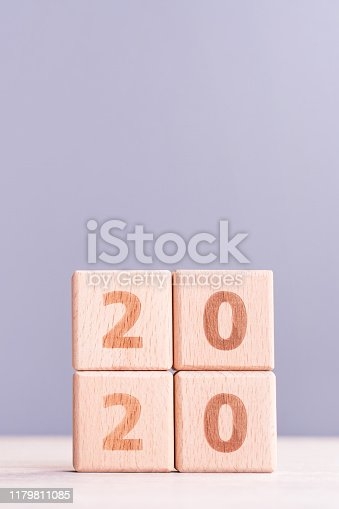 1054929988 istock photo Abstract 2020, 2019 New year target plan design concept - wood blocks cubes on wooden table and pastel blue background, close up, blank copy space. 1179811085