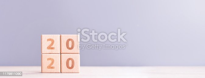 istock Abstract 2020, 2019 New year target plan design concept - wood blocks cubes on wooden table and pastel blue background, close up, blank copy space. 1179811090