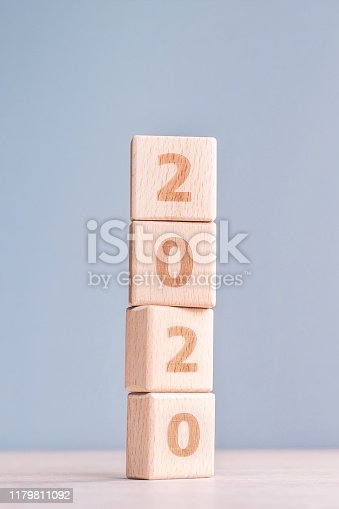 1054929988 istock photo Abstract 2020, 2019 New year target plan design concept - wood blocks cubes on wooden table and pastel blue background, close up, blank copy space. 1179811092