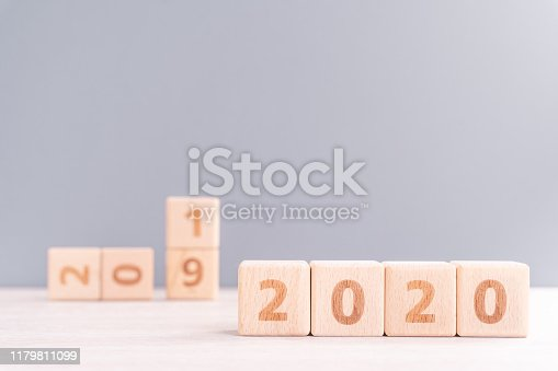istock Abstract 2020, 2019 New year target plan design concept - wood blocks cubes on wooden table and pastel blue background, close up, blank copy space. 1179811099