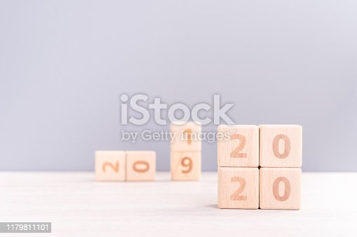 istock Abstract 2020, 2019 New year target plan design concept - wood blocks cubes on wooden table and pastel blue background, close up, blank copy space. 1179811101