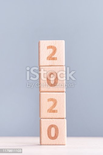 1054929988 istock photo Abstract 2020, 2019 New year target plan design concept - wood blocks cubes on wooden table and pastel blue background, close up, blank copy space. 1179811103