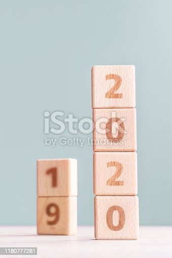 1054929988 istock photo Abstract 2020, 2019 New year target plan design concept - wood blocks cubes on wooden table and pastel green background. 1180777261