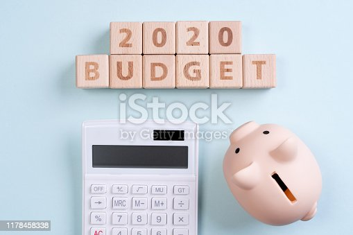 1170746979 istock photo Abstract 2020 financial goal design concept - geometric wood blocks cubes on blue table background with piggy bank. 1178458338