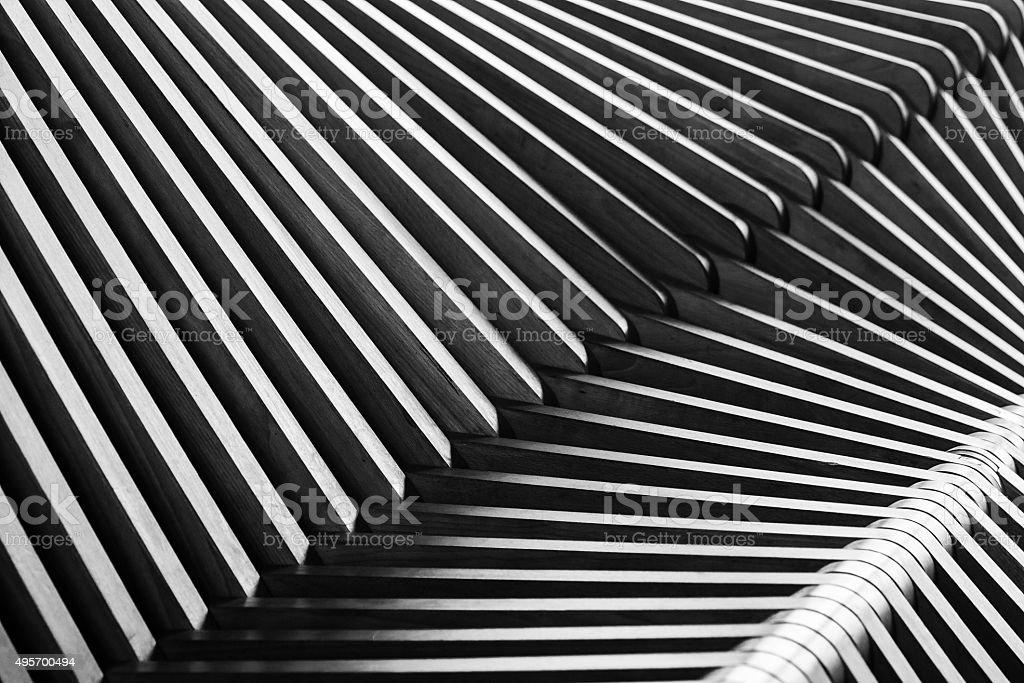 Black and white shiny curved wooden structure on bench. Abstract...