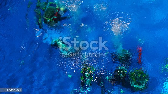 istock Abstract background design template. Blue underwater surface, silhouettes of divers and air bubbles. 1212344074