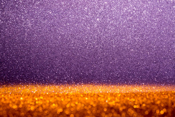 Abstract background filled with shiny gold and purple glitter stock photo