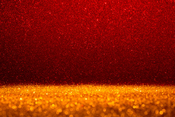 Abstract background filled with shiny gold and red glitter stock photo
