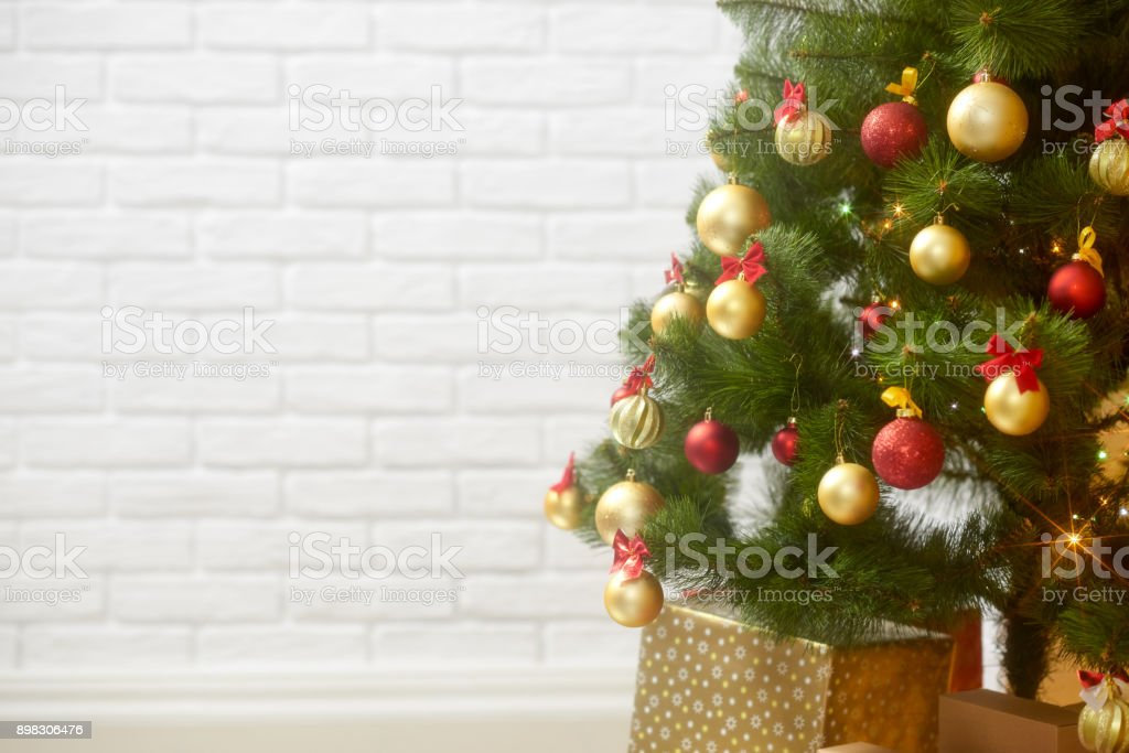 abstract background from christmas tree and blank brick wall, classic white interior backdrop, copy space for text, winter holiday concept stock photo