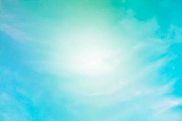 Abstract background of a vibrant clear blue teal sky with soft white clouds forming a frame for text stock photo
