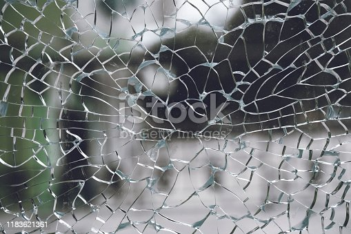 882262948 istock photo Abstract background of cobweb cracks The texture of the broken cracks. Close-up of a cracked glass. Dirty scratched broken glass of a office door 1183621361