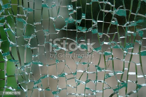 882262948 istock photo Abstract background of cobweb cracks The texture of the broken cracks. Close-up of a cracked glass. Dirty scratched broken glass of a office door 1183621370