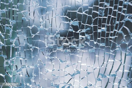 882262948 istock photo Abstract background of cobweb cracks The texture of the broken cracks. Close-up of a cracked glass. Dirty scratched broken glass of a office door 1183621537