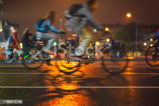 929609038istockphoto Abstract background of colorful group of bicyclists, night city street, blur effect, unrecognizable people. Sport, fitness and healthy lifestyle concept. For backdrop 1186913734