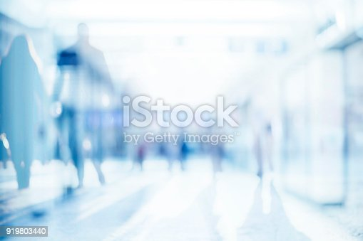 istock Abstract background of empty space with silhouettes of people passing by 919803440