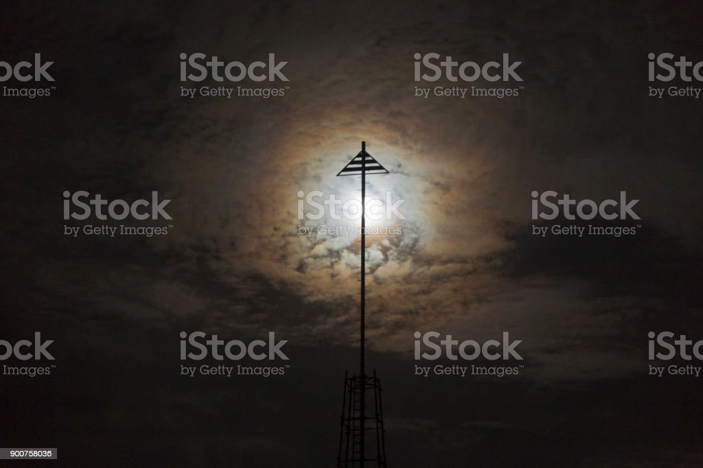 Abstract Background of Full Moon Rising behind Iron Post Silhouette on Torrey Pines Gliderport in San Diego stock photo