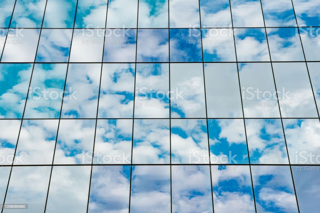 Abstract Background of Glass Office Building Reflecting a Cloudy Sky This is a photograph of a mirrored glass office building exterior reflecting an overcast sky in New Orleans, Louisiana, USA. Abstract Stock Photo