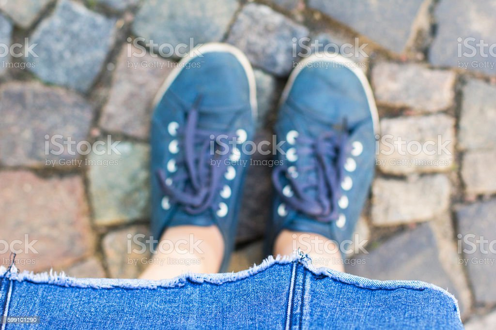 abstract background traveler legs and blue boots on the cobblestones stock photo