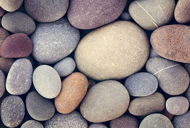 abstract background with dry round pebble stones macro - river stock photos and pictures