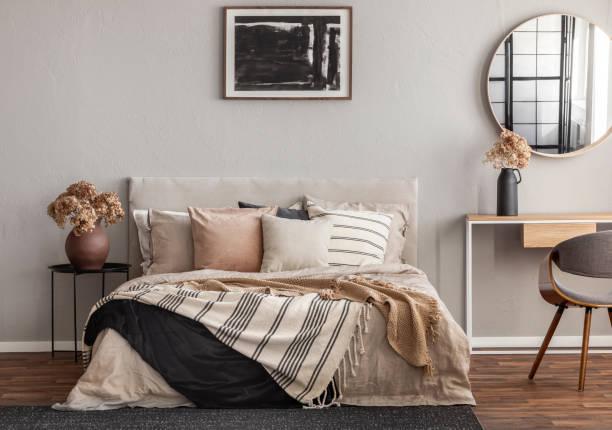 abstrakte schwarze ölgemälde im rahmen auf leere beige wand von gemütlichen schlafzimmer - schlafzimmer stock-fotos und bilder