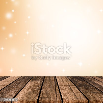 1034181324istockphoto abstract blur beautiful gold  color with glow light and snow fall on christmas background and plank wooden texture floor for show,advertise,promote product concept 1083383870