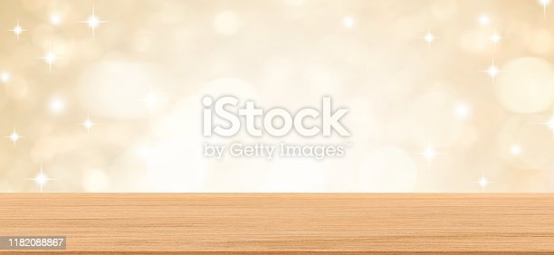 530427918 istock photo abstract blur beautiful gold metal color and glittering bokeh light background with modern brown wood tabletop for show,ads,design product on display in the christmas festival and happy new year season concept 1182088867