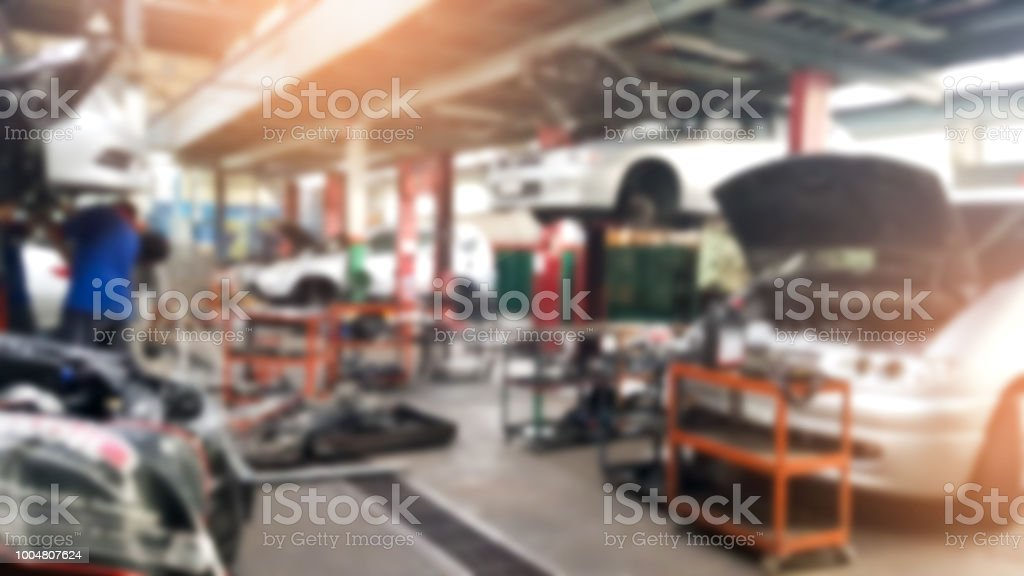 Abstract blur car technicians repairing cars in workshop service station background.Auto repair shop in bokeh, defocused background stock photo