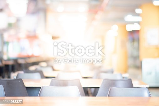 Abstract blur empty tables and chairs in cafeteria or food court of department store. Blurred canteen dining hall with defocused effect. Background or backdrop for restaurant eating space concept