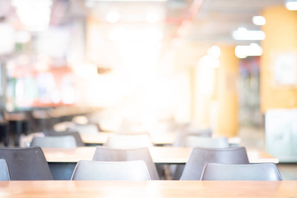 abstract blur empty tables and chairs in cafeteria or food court of department store. blurred canteen dining hall with defocused effect. background or backdrop for restaurant eating space concept - banchi scuola foto e immagini stock