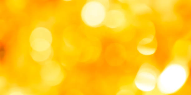 abstract blur glowing yellow color panoramic background with double exposure bokeh light for happy new year and merry christmas celebration festival design element concept stock photo