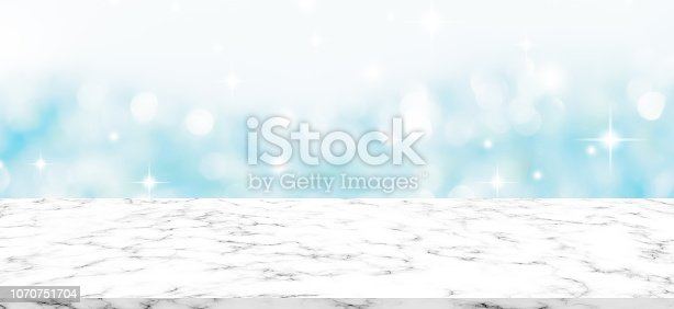 1047386704istockphoto abstract blur luxury blue bokeh light with glitter snowfall and twinkle star shine wallpaper and white marble counter table top background texture for promote and show or advertise product on display concept 1070751704