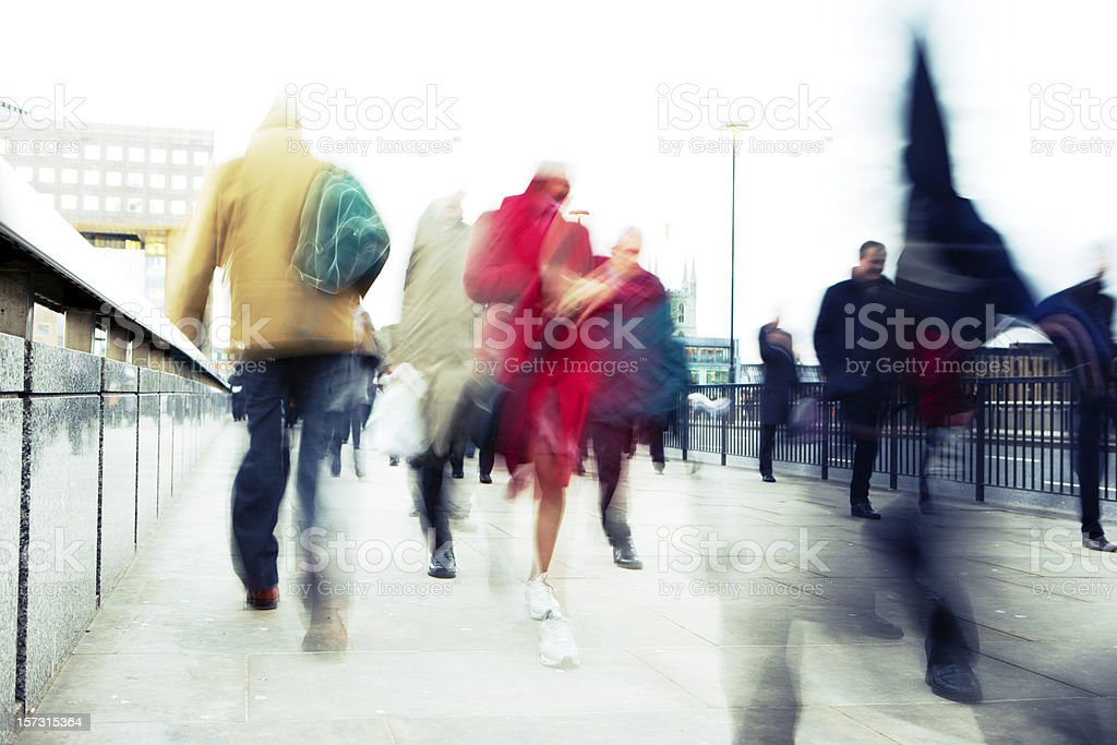 Abstract blur of commuters and pedestrians walking on busy pavement royalty-free stock photo