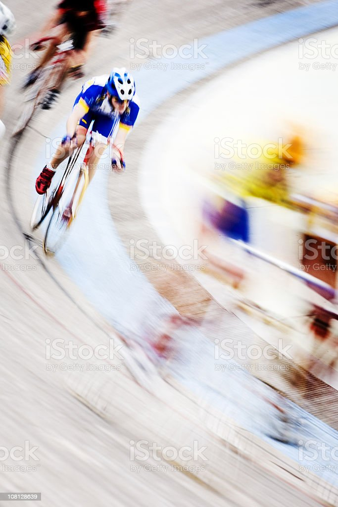 Abstract blur of professional cyclists speeding around a velodrome curve stock photo