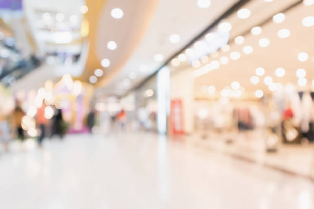 abstract blur people in modern shopping mall interior defocused background - shopping mall stock photos and pictures