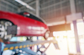 istock Abstract blur red car wheel alignment in progress at auto repair service centre background 1180105771