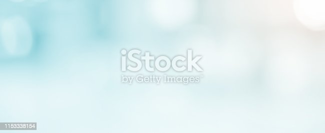 istock abstract blur soft focus blue color modern workplace background with shine light for design concept 1153338154