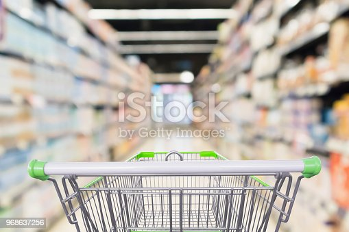 836871040 istock photo Abstract blur supermarket aisle defocused background with empty green shopping cart 968637256