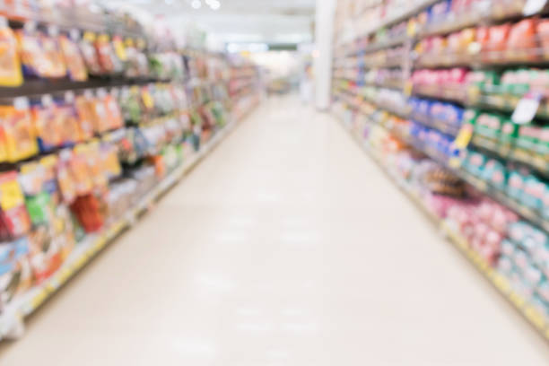 Abstract blur supermarket discount store aisle and product shelves interior defocused background Abstract blur supermarket discount store aisle and product shelves interior defocused background snack aisle stock pictures, royalty-free photos & images