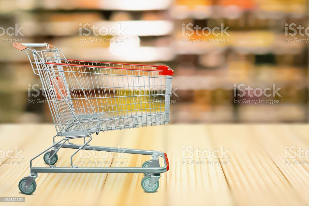 Abstract blur supermarket shelves defocused background with shopping cart on wood table - Royalty-free Abstract Stock Photo