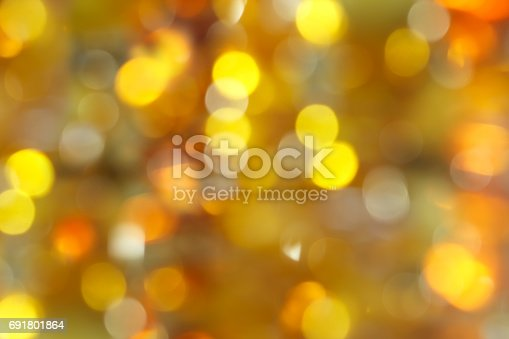 istock abstract blurred background - dark yellow, green and orange shimmering lights bokeh of amber 691801864
