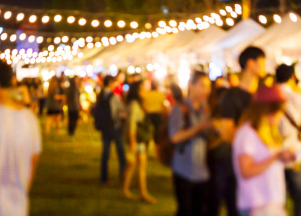 abstract blurred background of people shopping at night market - traditional festival stock photos and pictures