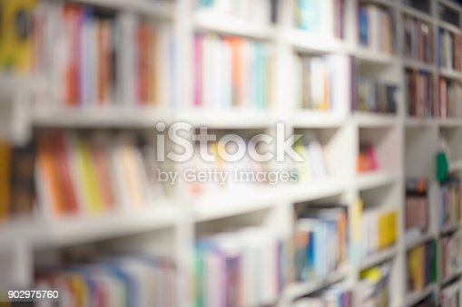 istock Abstract blurred bookshelves with books, manuals and textbooks on bookshelves in library or in bookstore, for backdrop. Concept of reading, education 902975760